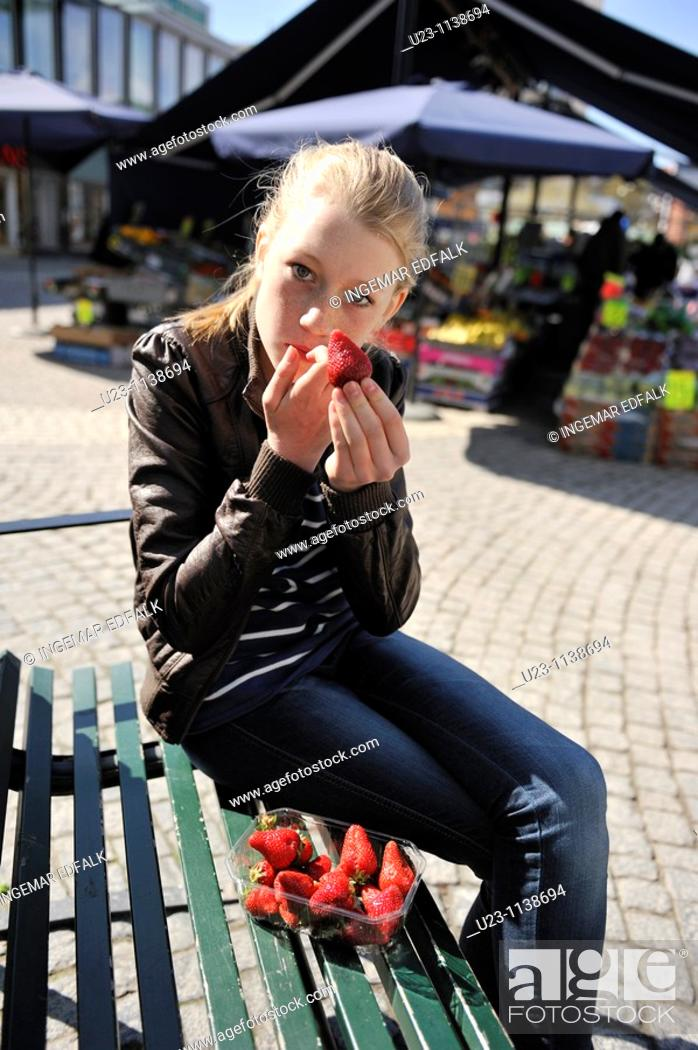 Stock Photo: Young girl eating one of the seasons first strawberries.