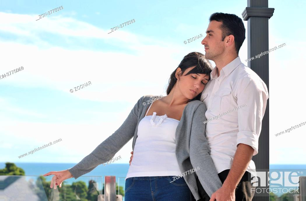 Stock Photo: happy young couple in love have romance relax on balcony outdoor with ocean and blue sky in background.