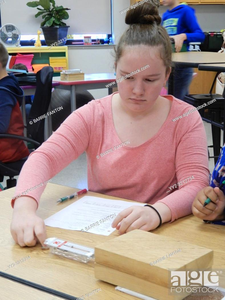 Stock Photo: 8th Grade Girl Doing Science Friction Experiment, Wellsville, New York, USA.