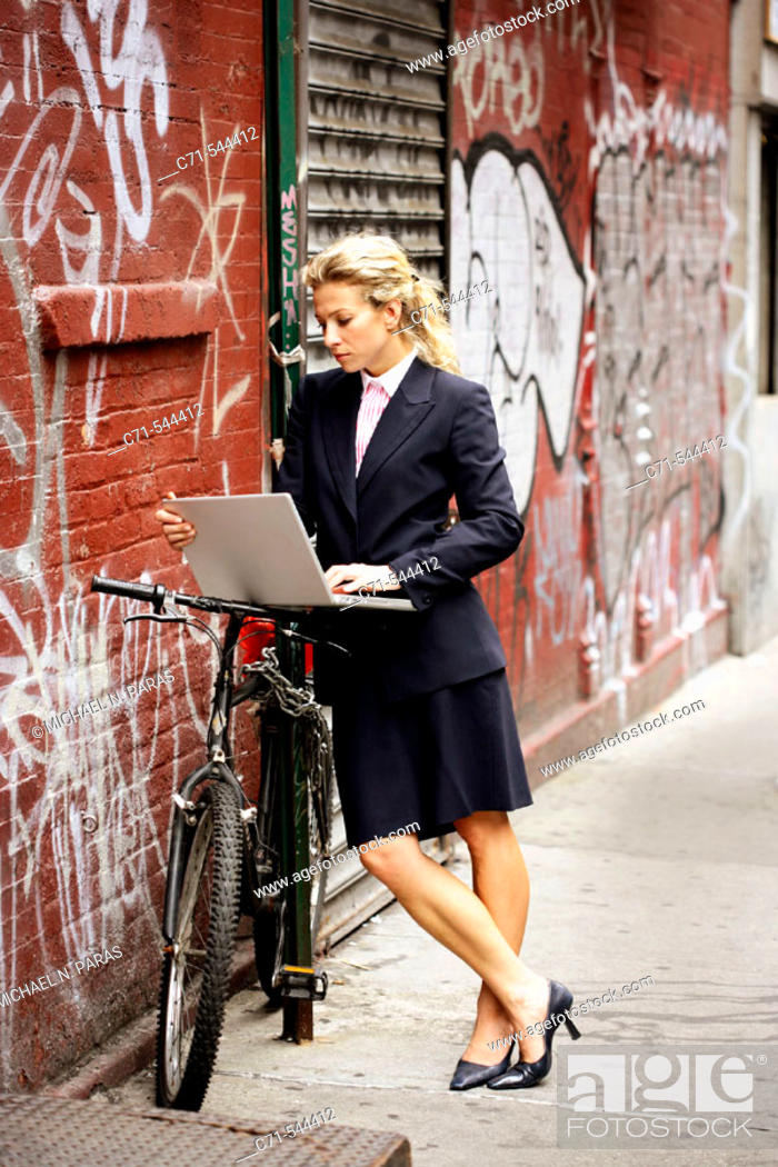 Stock Photo: Caucassian businesswoman working on laptop leaning on bicycle against a graffiti wall.