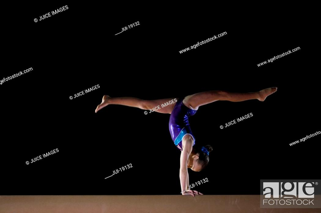 Stock Photo: Female gymnast performing handstand on balance beam, side view.