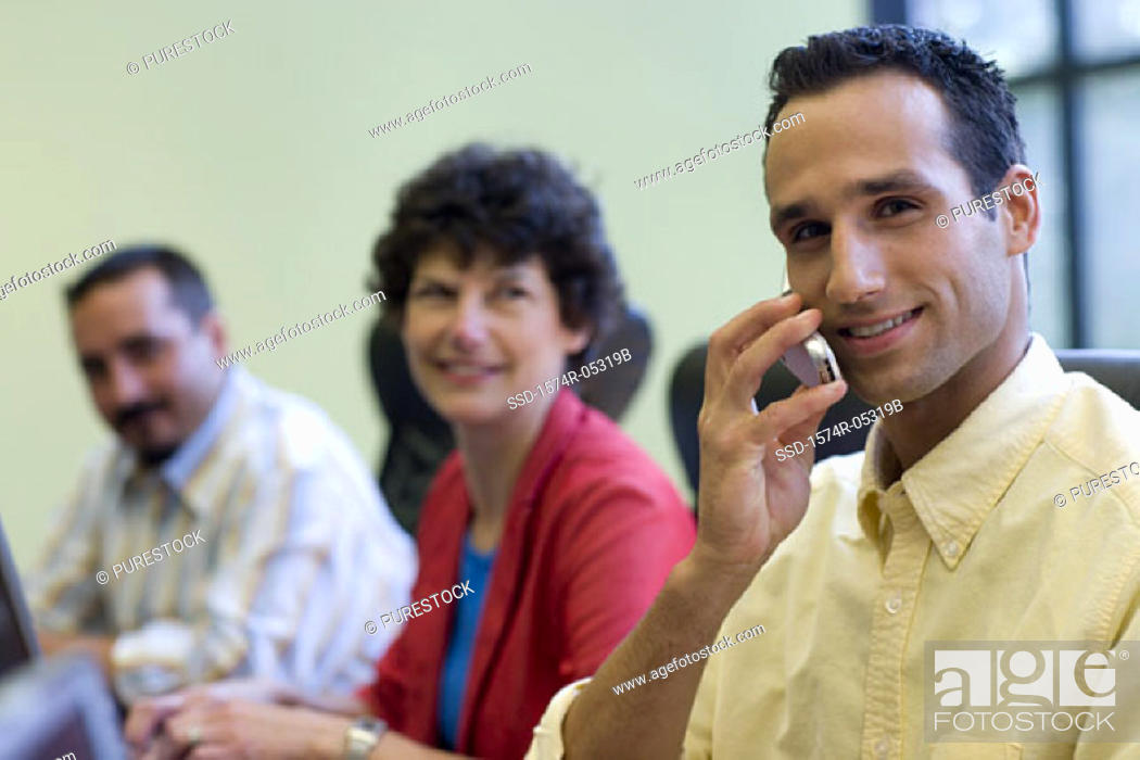 Stock Photo: Portrait of two businessmen and a businesswoman sitting in a conference room.
