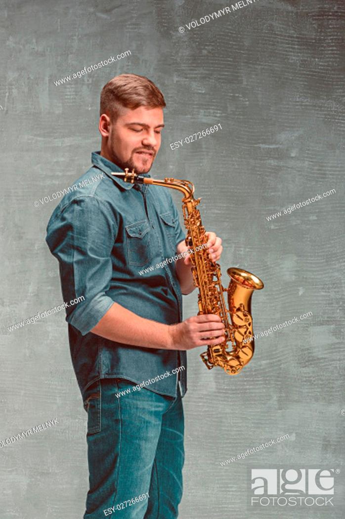 Imagen: Happy saxophonist with sax on gray studio background.