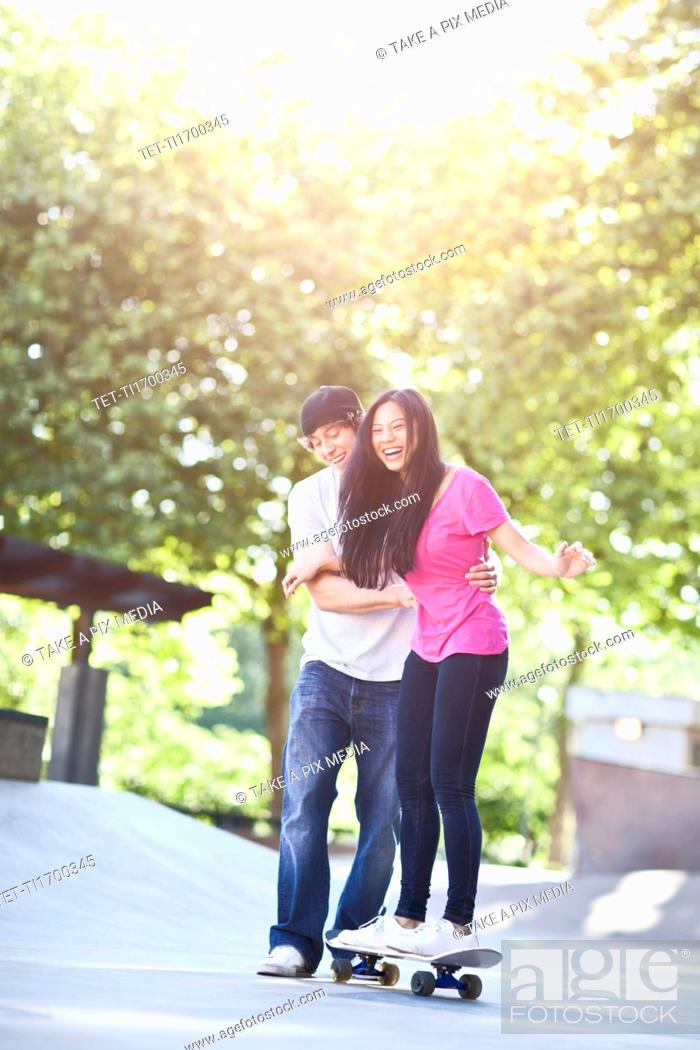 Stock Photo: Young multi racial couple skateboarding.