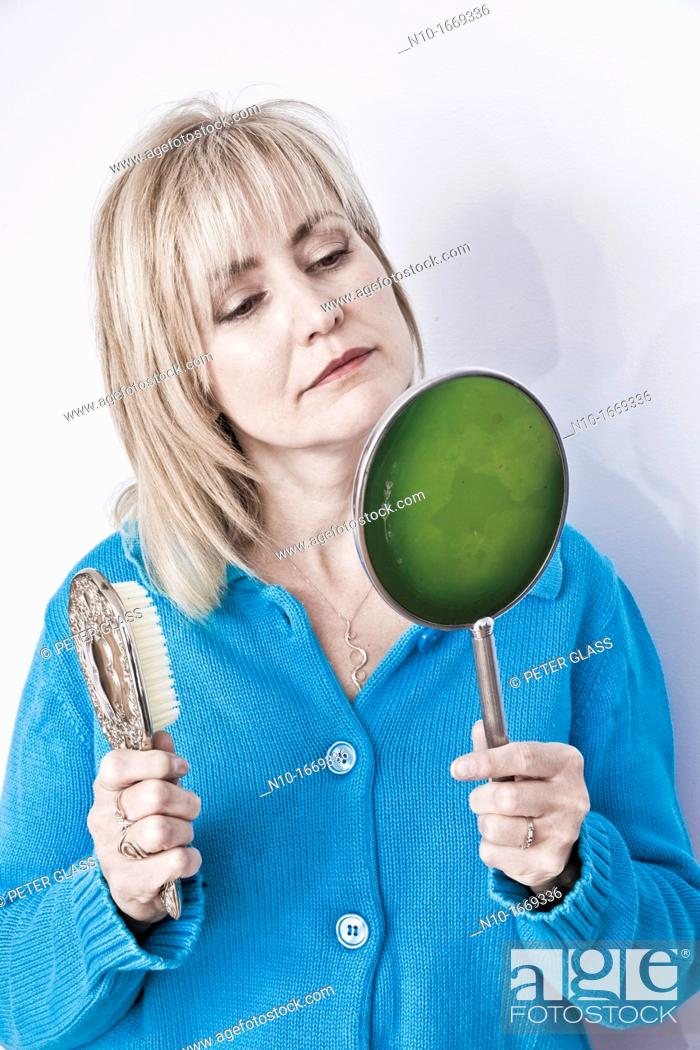 Stock Photo: Middle-age blond woman holding a hairbrush and a hand mirror.