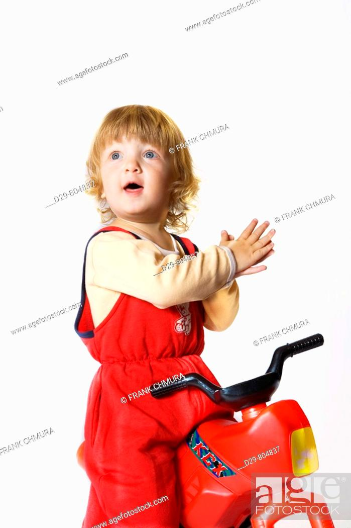Stock Photo: BOY RIDING TOY TRICYCLE.