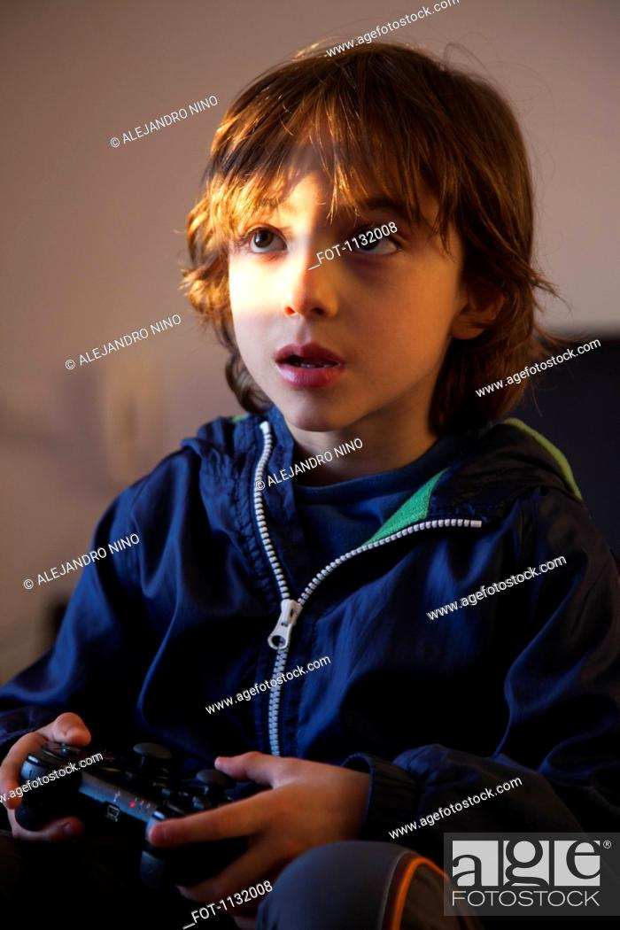 Stock Photo: A young boy holding a video game controller looking concentrated.