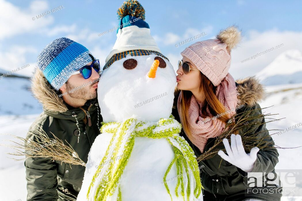 Stock Photo: Spain, Asturias, couple kissing a snowman.