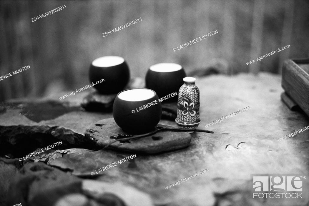 Stock Photo: Tea cups placed on rock surface.
