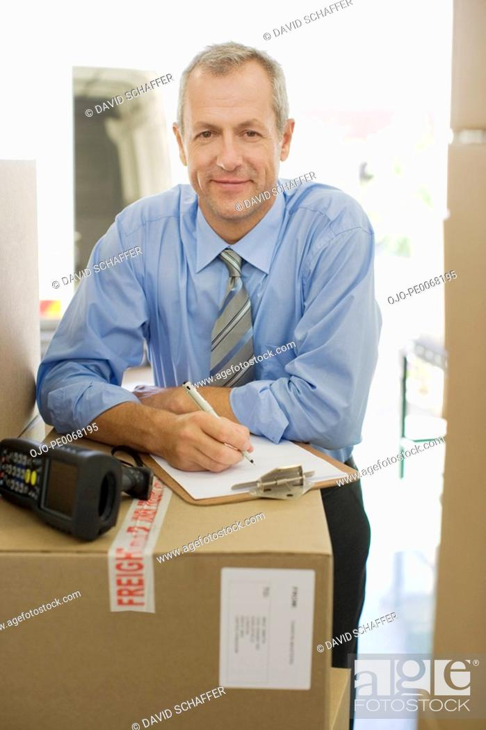 Stock Photo: Businessman with clipboard leaning on cardboard box.