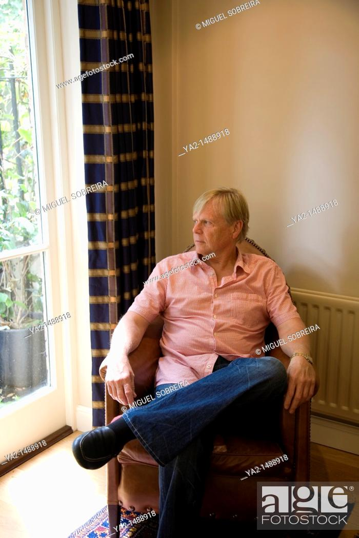 Stock Photo: Mature man Looking out Window from Armchair.