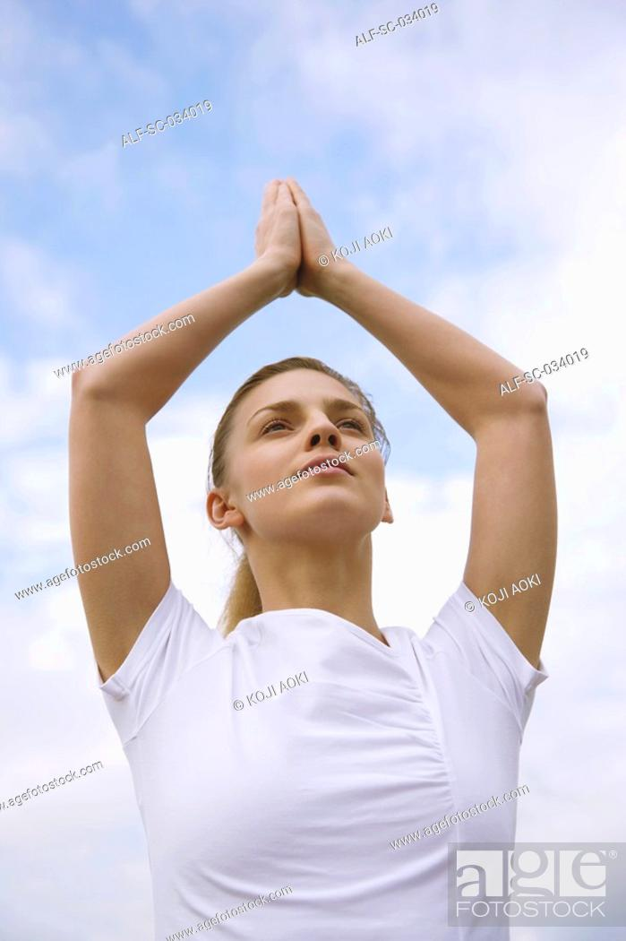 Stock Photo: Young Woman meditating in a tree pose.