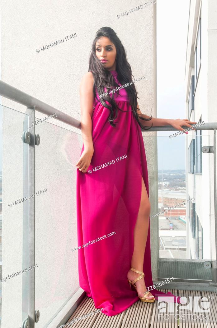 Stock Photo: Beautiful Indian woman in hot pink dress standing on the blacony looking away.