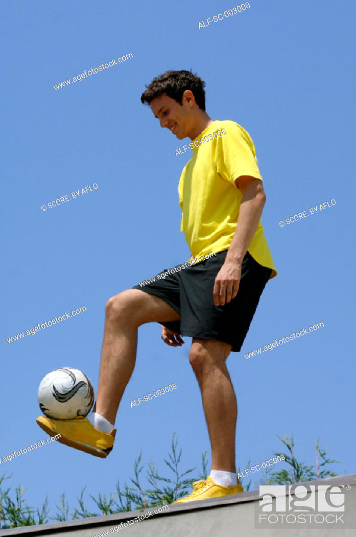 Stock Photo: Teenage boy juggling soccer ball.