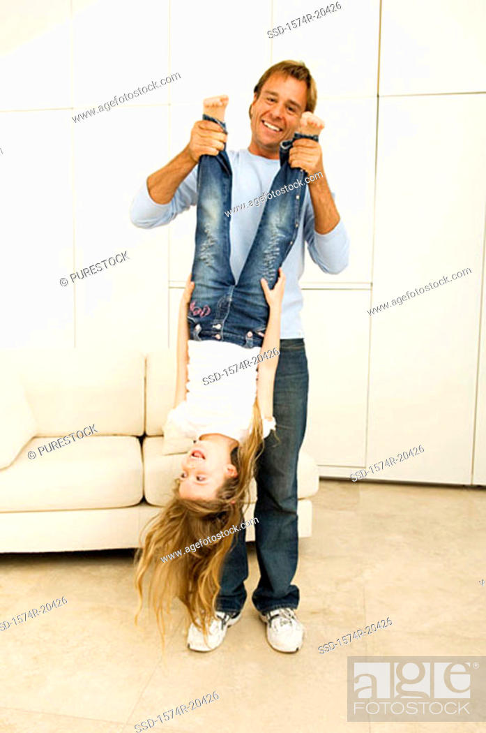 Stock Photo: Portrait of a young man holding his daughter upside down by her feet.