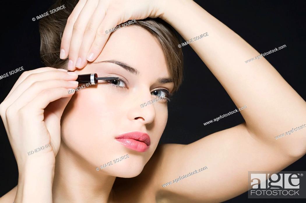 Stock Photo: Woman applying eyeliner.