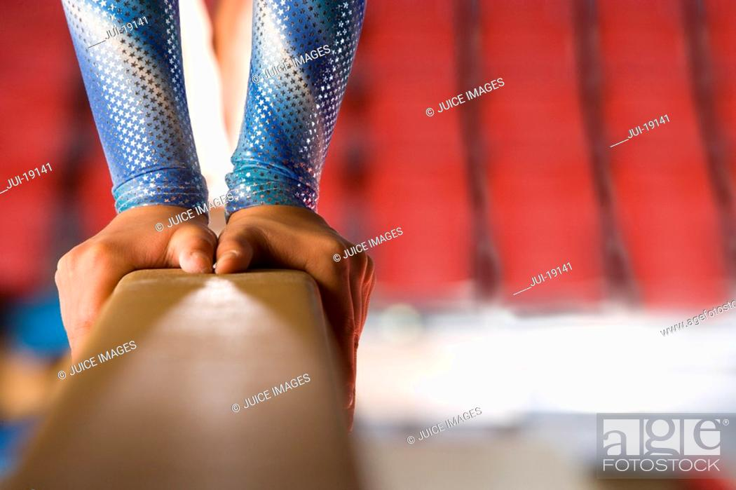 Stock Photo: Young female gymnast performing on balance beam, low section.