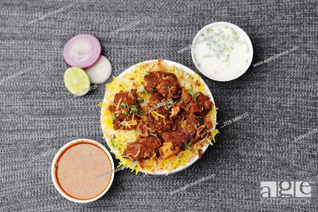 Stock Photo: Hyderabadi chicken biryani and sauces.