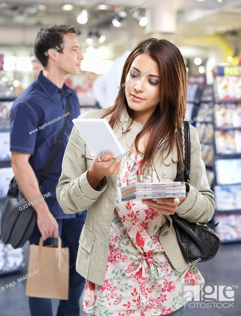 Stock Photo: Woman looking at CDs with man in background.