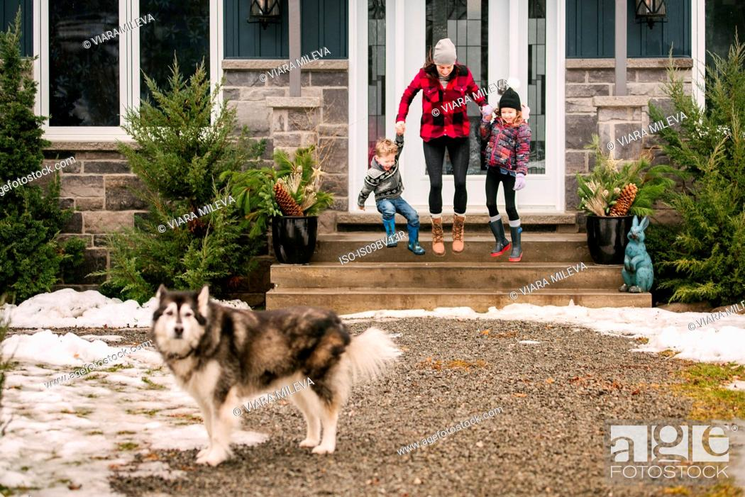 Stock Photo: Family with pet dog leaving house to go out.