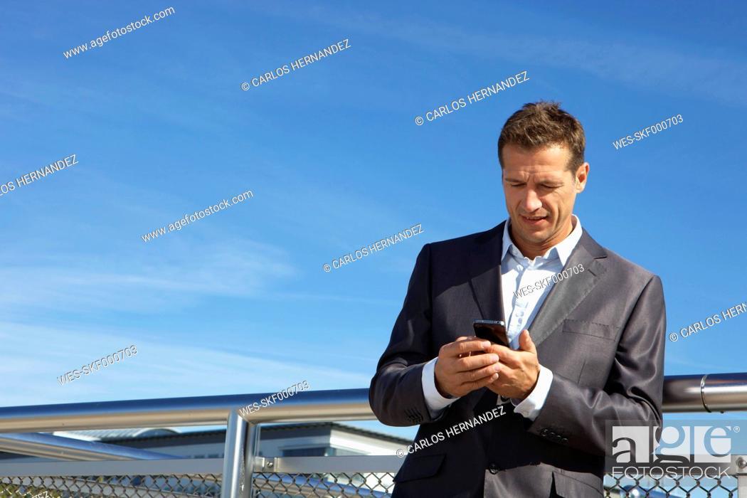 Stock Photo: Germany, Bavaria, Munich, Businessman using cell phone.