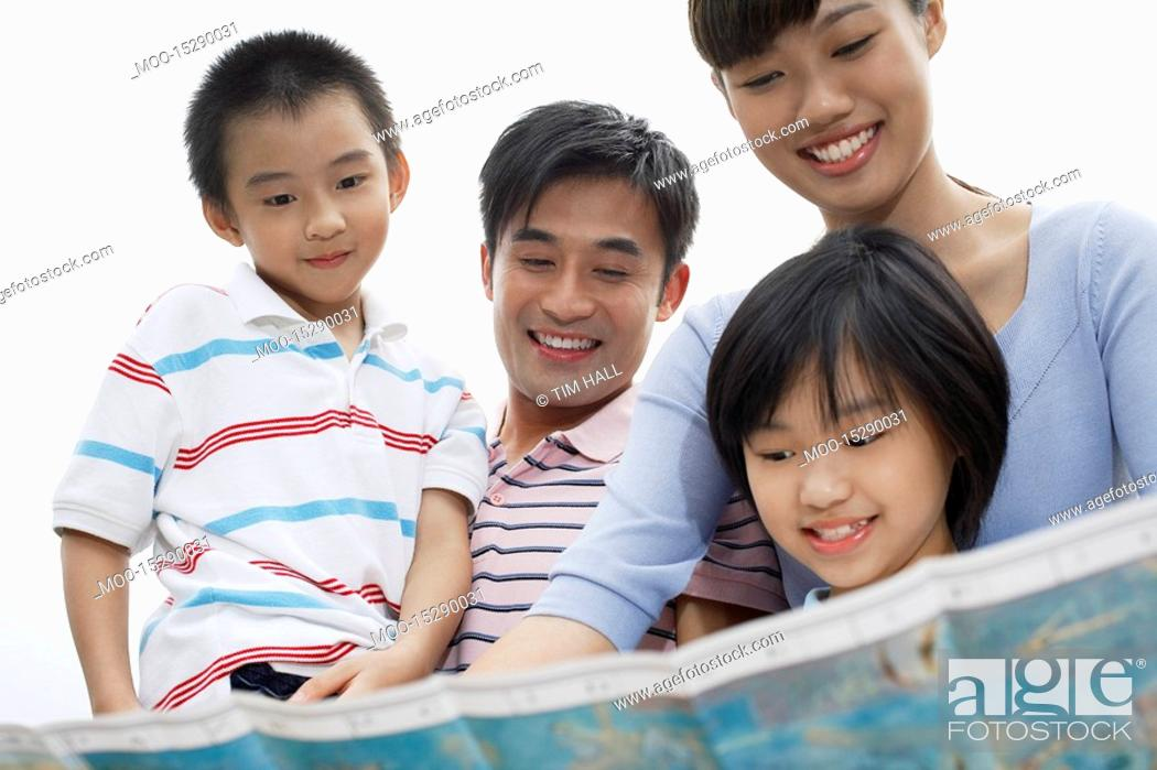 Stock Photo: Family including boy and girl 7-9 reading map outdoors.