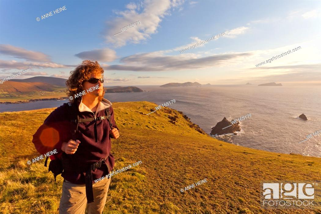 Stock Photo: man standing on cliffs with islands in background lit from behind, dingle peninsula, ireland.