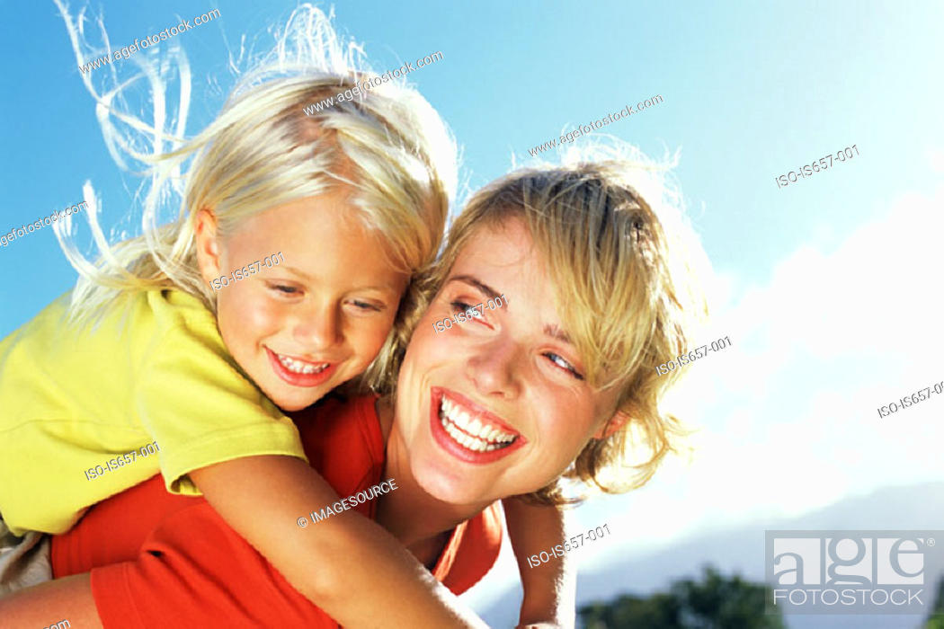 Stock Photo: Mother giving daughter a piggyback.