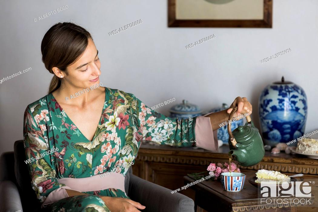 Stock Photo: Young woman sitting in an armchair at home pouring tea into a cup.