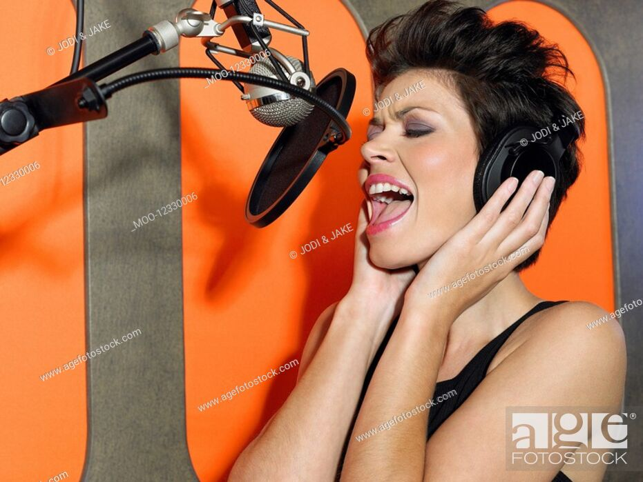 Stock Photo: Young woman singing in studio portrait.