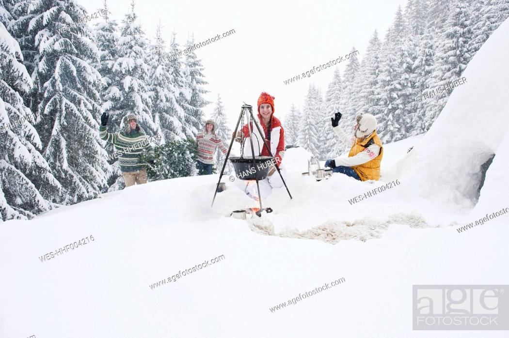 Stock Photo: Austria, Salzburg, Man and woman by fireplace, people carrying christmas tree in background.