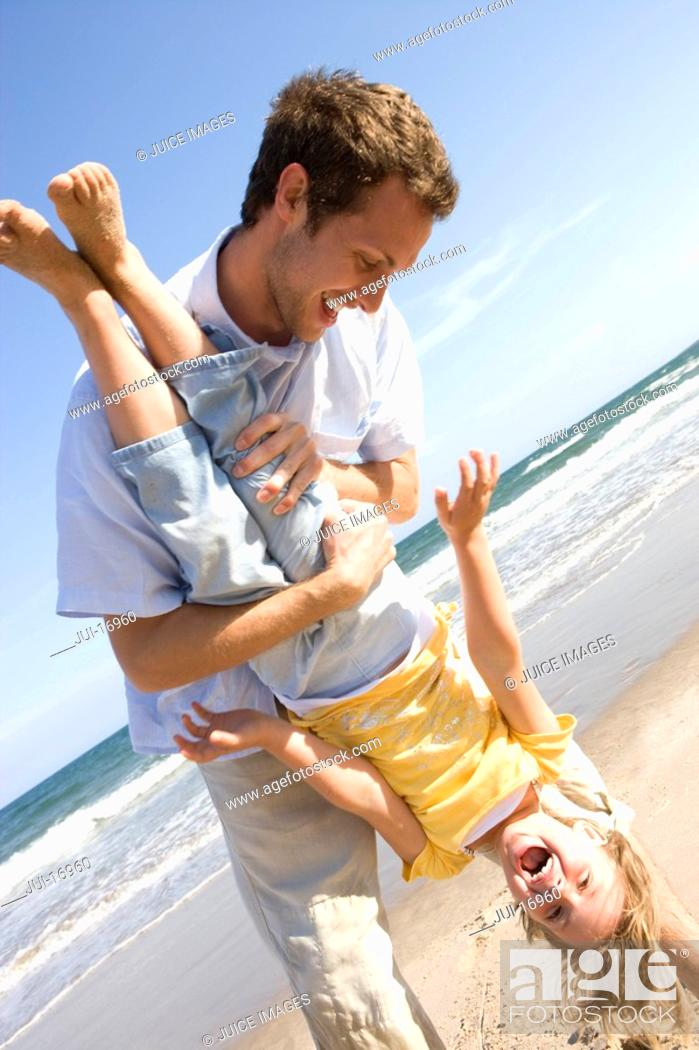 Stock Photo: Father holding daughter upside down on beach.