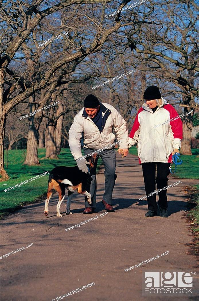 Stock Photo: elderly couple walking their dog.