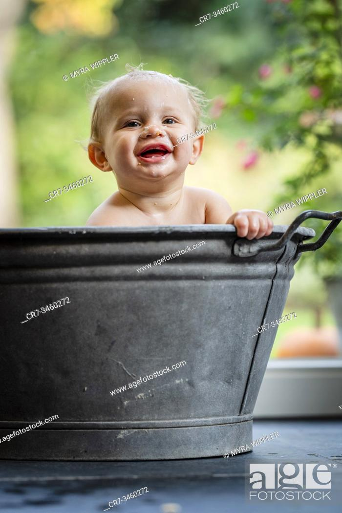 Stock Photo: Baby boy having fun in a metal bath tub with bubbles.