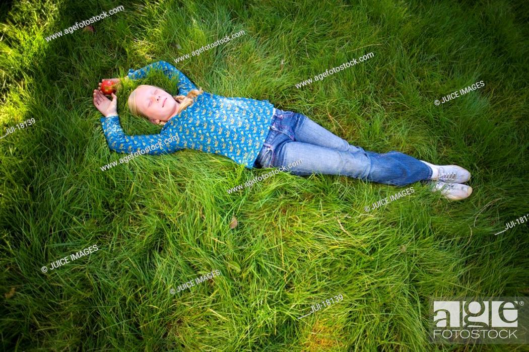 Stock Photo: Teenage girl 11-13 lying in grass with eyes closed, elevated view full frame.