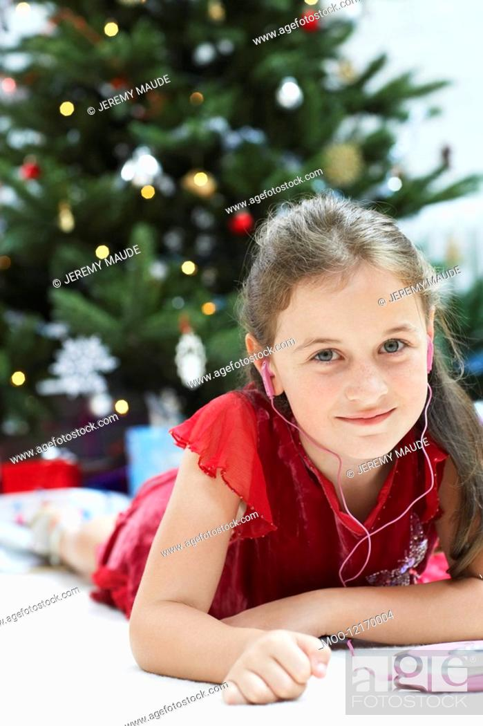 Stock Photo: Little Girl lying down by christmas tree Listening to CD Player portrait.