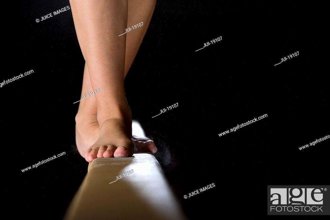 Stock Photo: Female gymnast performing on balance beam, low section.