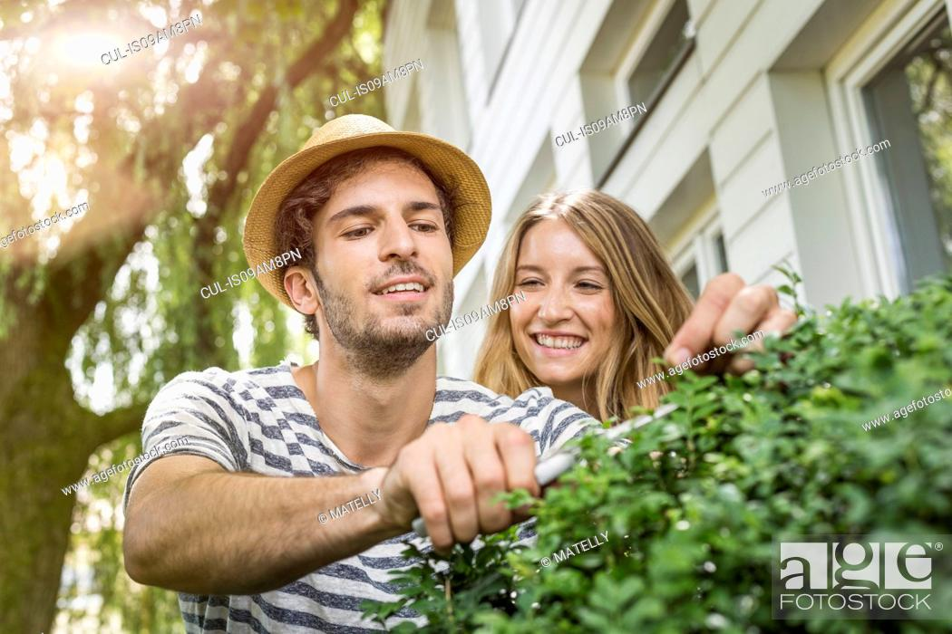Stock Photo: Young couple pruning bush outside house.