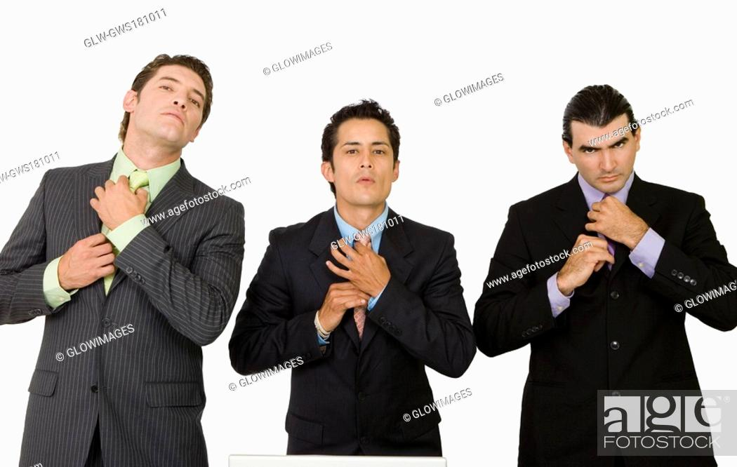 Stock Photo: Portrait of three businessmen adjusting their ties.