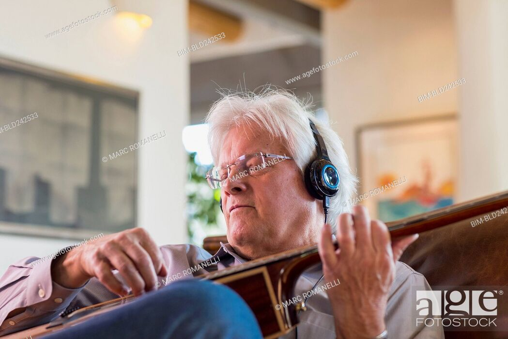 Stock Photo: Caucasian man listening to headphones and playing guitar.
