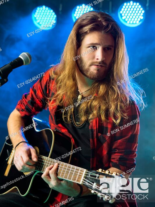 Stock Photo: Photo of a young man with long hair and a beard playing an acoustic guitar on stage with lights and concert atmosphere.