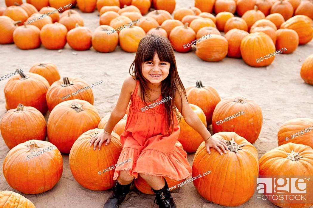 Stock Photo: Portrait of girl sitting on pumpkin in farmyard.