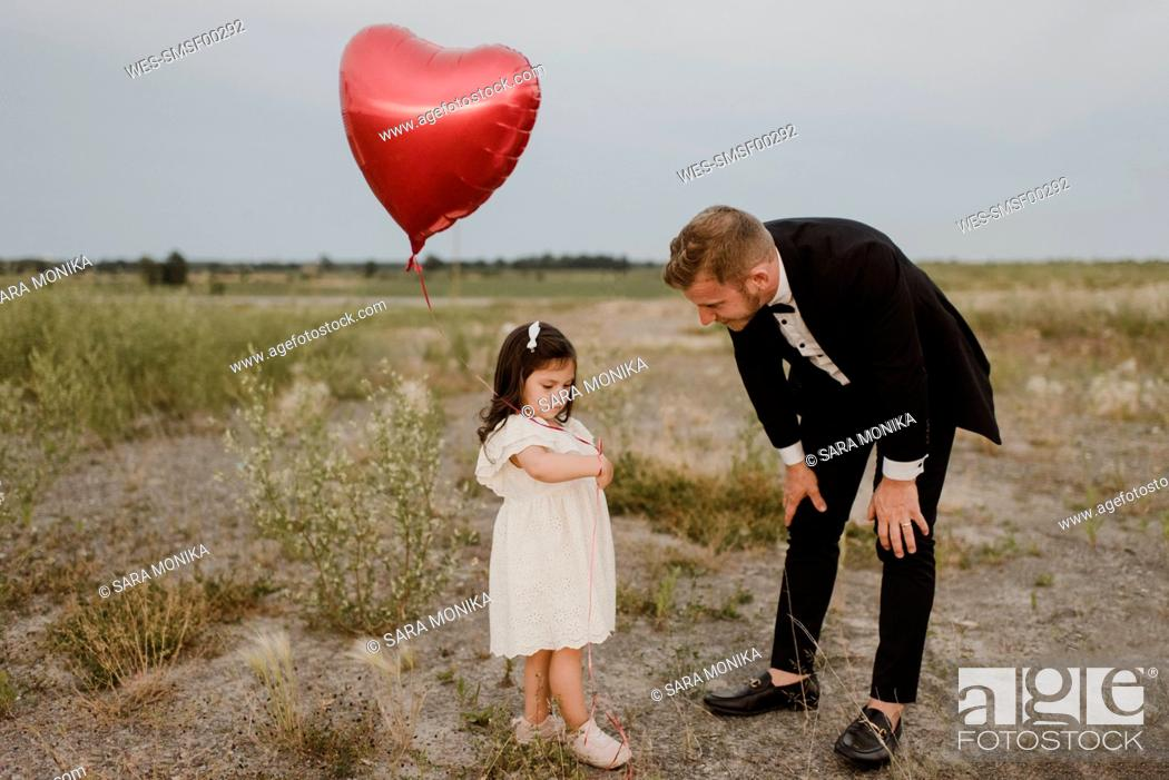 Stock Photo: Father talking to sad daughter with heart shape balloon in field against clear sky.