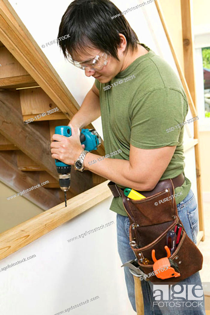 Stock Photo: Side profile of a young man drilling into a plank.