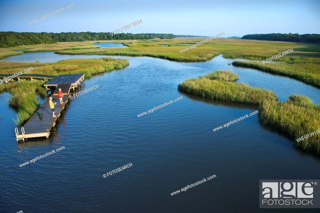 Stock Photo: Aerial view of two teenage boys fishing from dock in marshy lowlands of Bald Head Island, North Carolina.