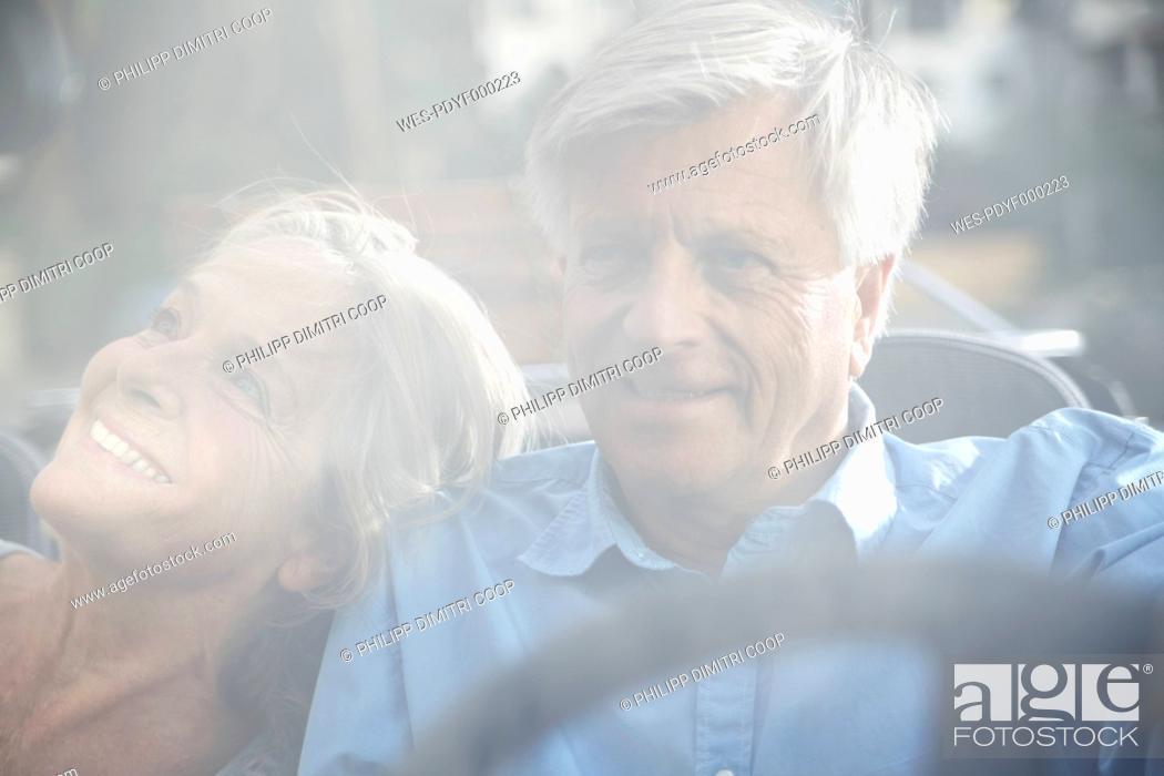 Stock Photo: Spain, Senior couple behind glass window, smiling.