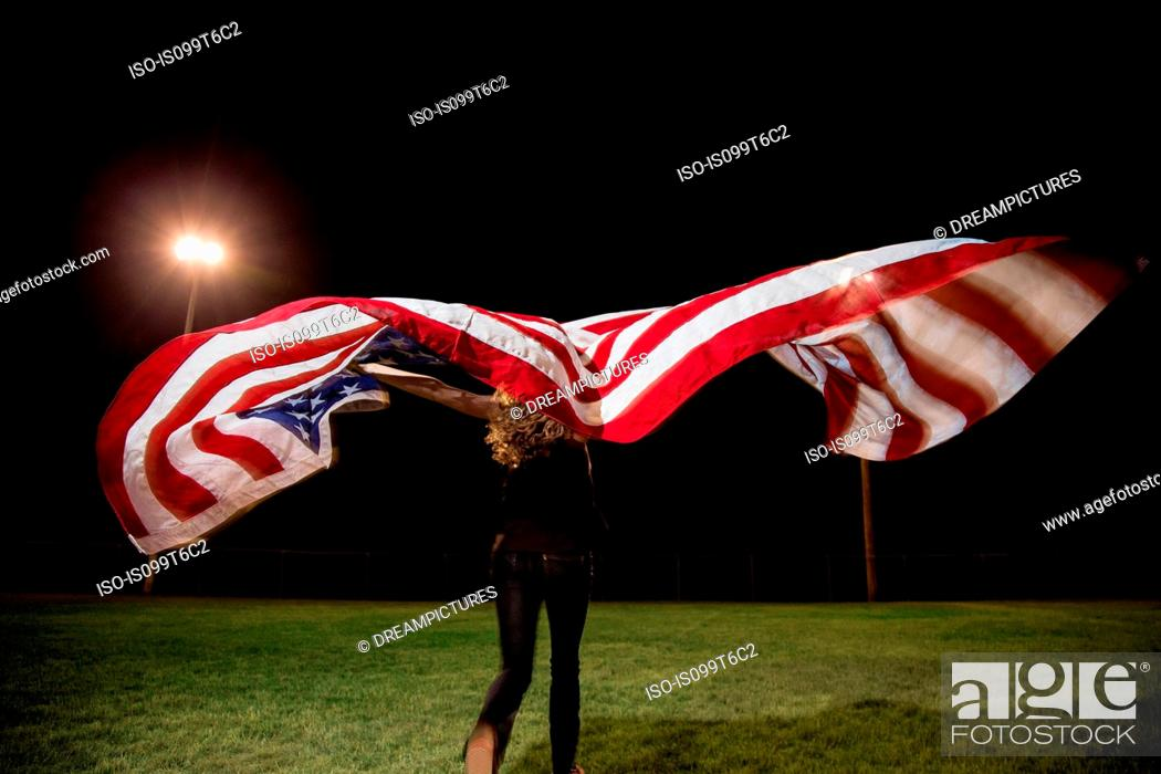 Photo de stock: Girl holding american flag at night.