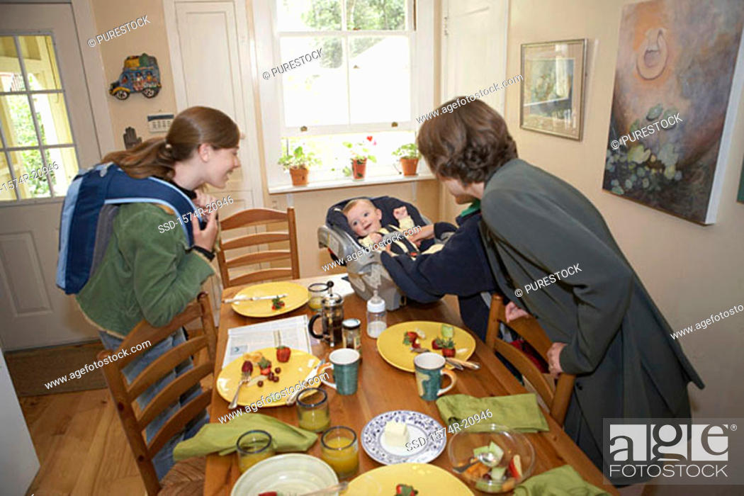 Stock Photo: Side profile of a mid adult woman and her daughter cuddling a baby boy at a dining table.