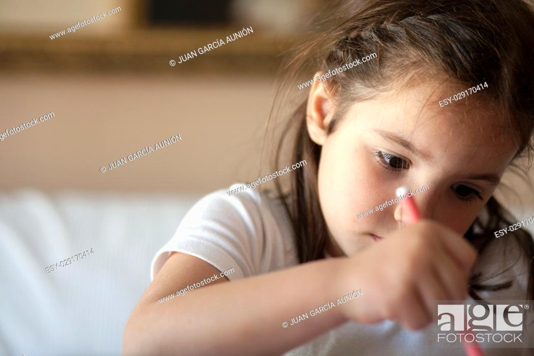 Photo de stock: Little girl draws with pink felt-tip pen on paper. Closeup portrait.