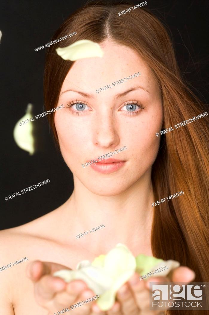 Stock Photo: woman with petals in hands.